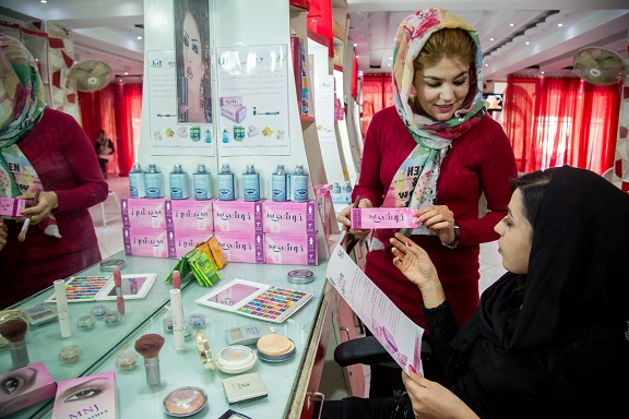 Beautician interacting with a client in a salon in Afghanistan about a health care product