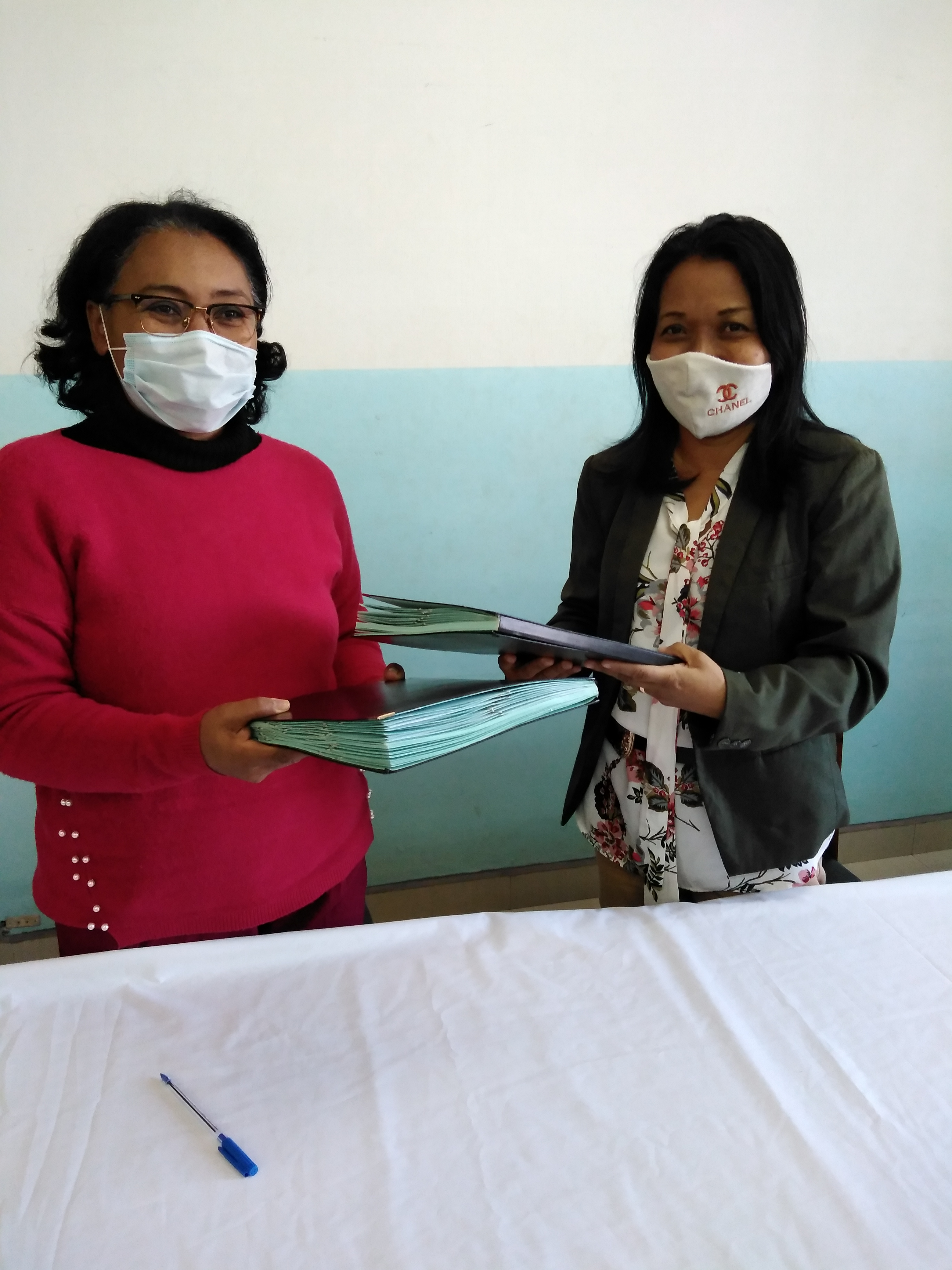 Two women handing over signed MOU documents