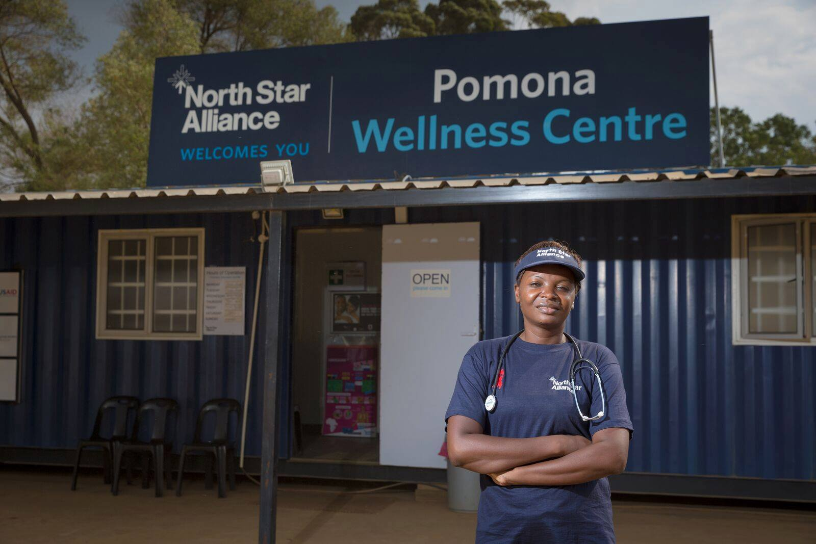 "A woman with a stethoscope stands in front of a blue box clinic that says ""North Star Alliance welcomes you"" and ""Pomona Wellness Centre"""