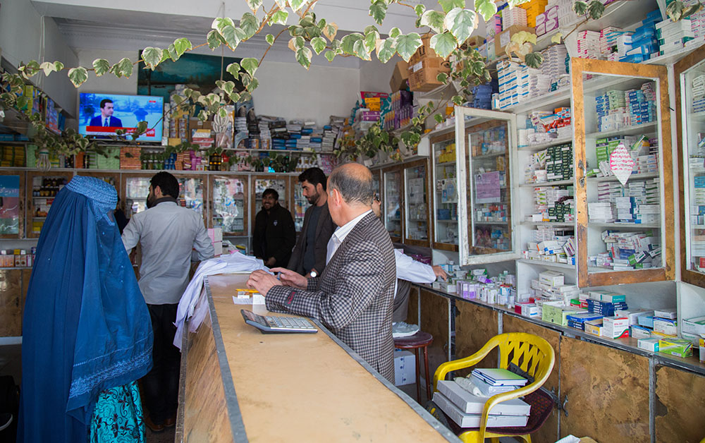 Woman in burka talking to person behind the counter in a pharmacy.