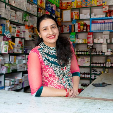 Female provider standing at the counter of her drug shop.