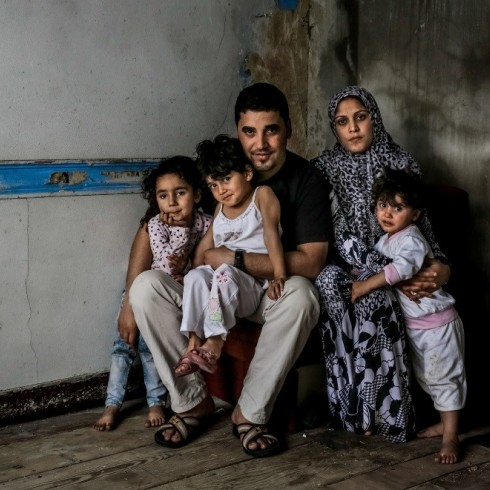 Father, mother and three children sitting in a dark room with no furniture.