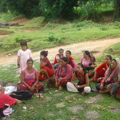 Community change agent conducting a session in a village sitting on the floor in a circle with other women