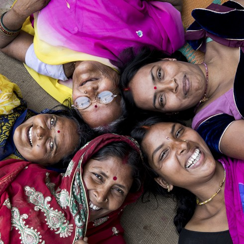Five Indian women lying down in a circle smiling up at the camera