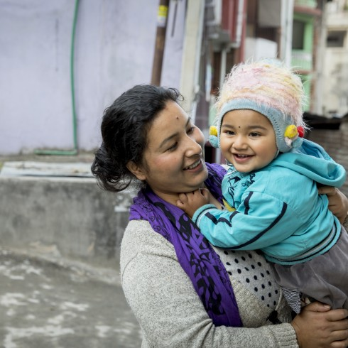 A women holds her child in Nepal.