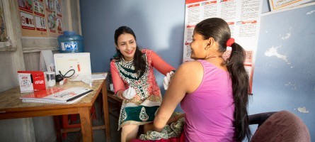 A woman prepares to dispense injectable contraception to a client