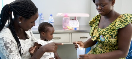 Image of a woman with her baby and a female health worker