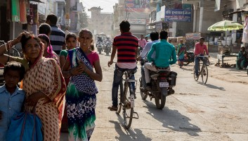 Photo of busy street in India with people walking and riding bikes.