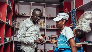 Drug shop owner in Lagos talking to a female client about a product.